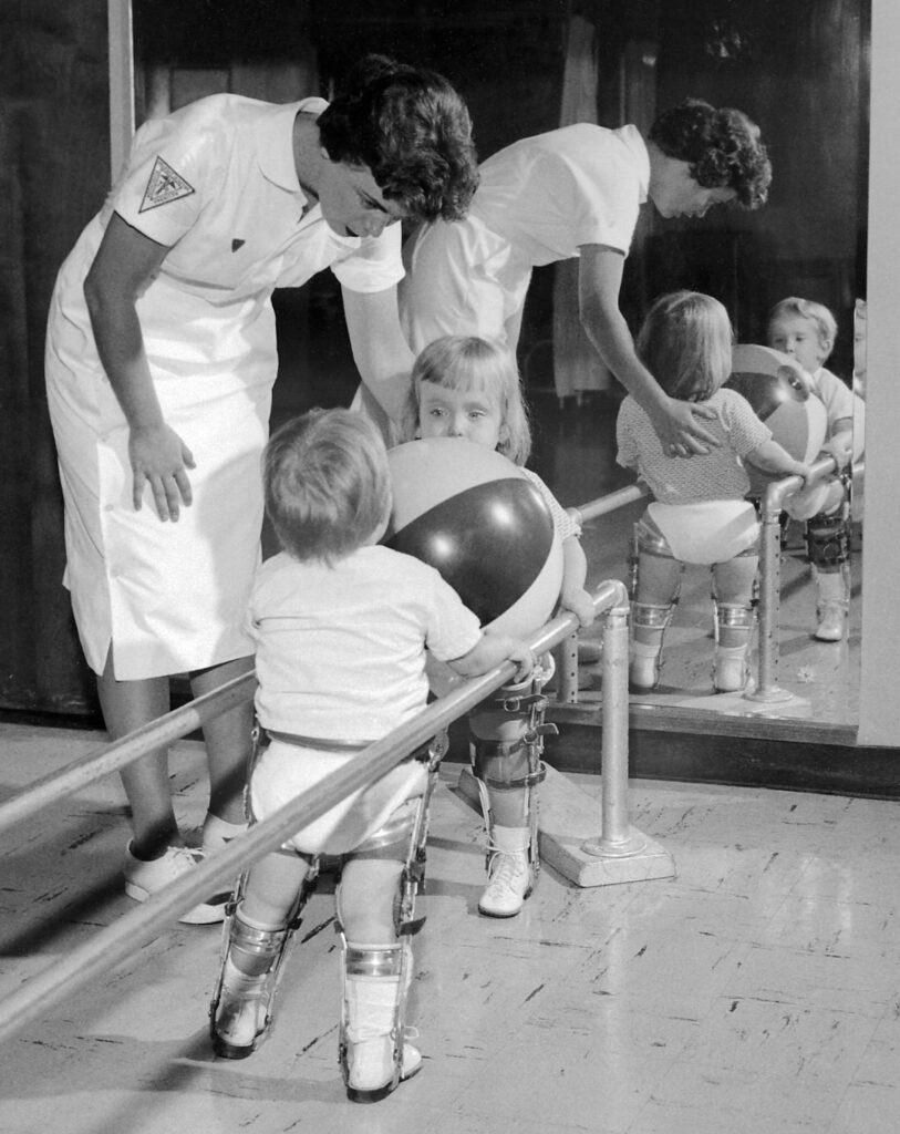 Physical therapist assisting two small children with polio holding on to rail. (Both are in braces). 1963 Charles Farmer